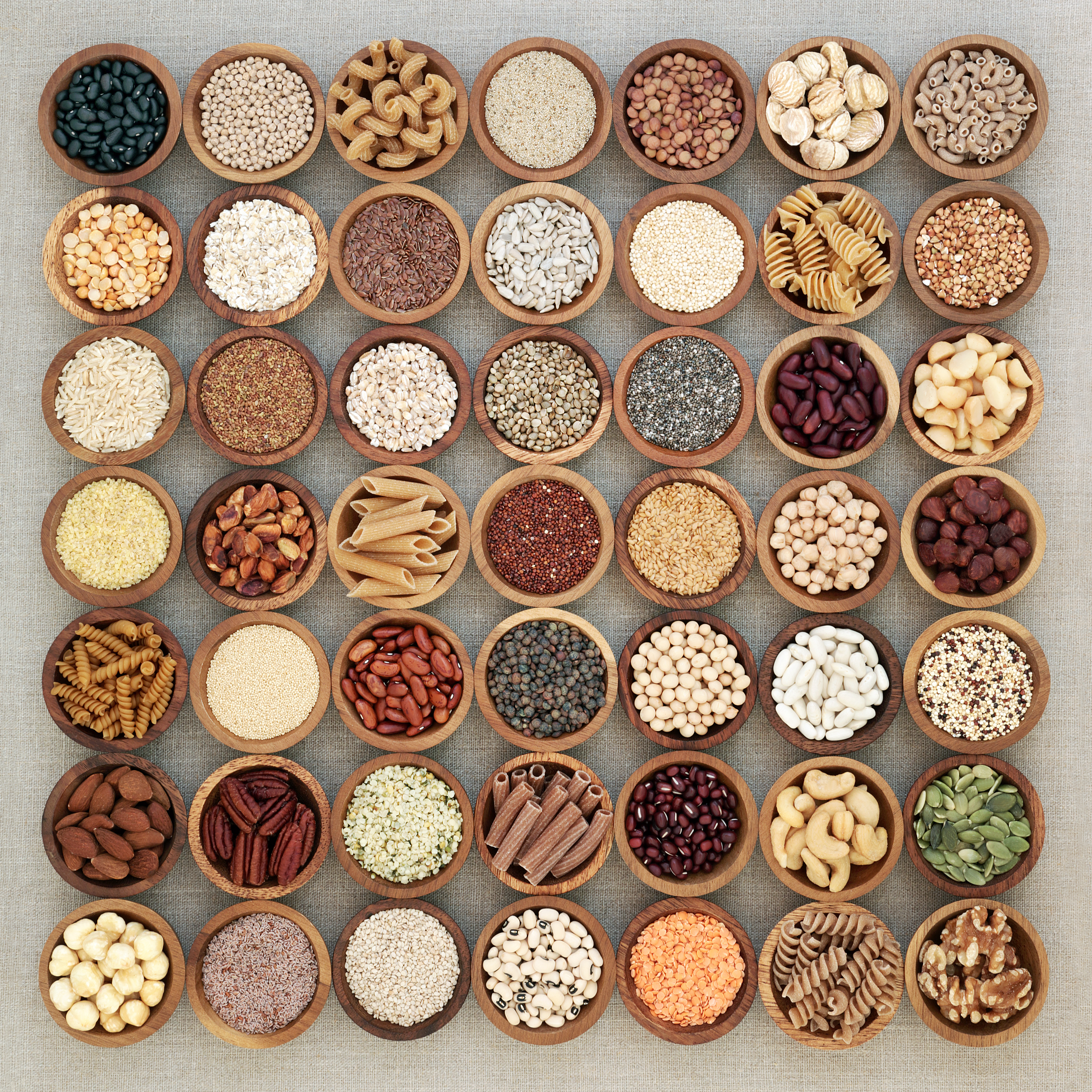 Vegan high protein dried health food collection with nuts, seeds, legumes, whole wheat pasta, grains and cereals. Foods high in fibre, antioxidants, anthocyanins, vitamins and minerals. Top view on hessian background.